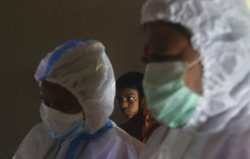 The Latest: India reports 933 deaths as cases near 2.1M